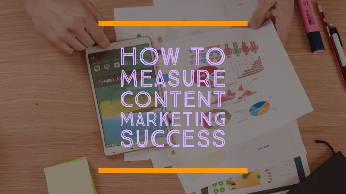 How to measure content marketing success: This title is laid over an image of a pair of hands pointing to a mobile phone and a sheet of paper full of charts