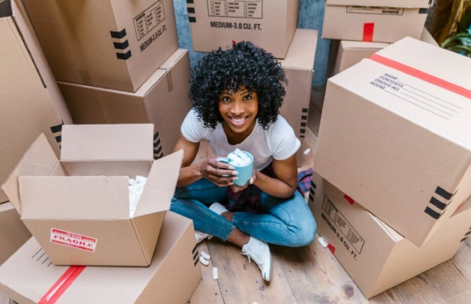 Woman surrounded by packing boxes, grinning and holding an undamaged mug full of packing foam